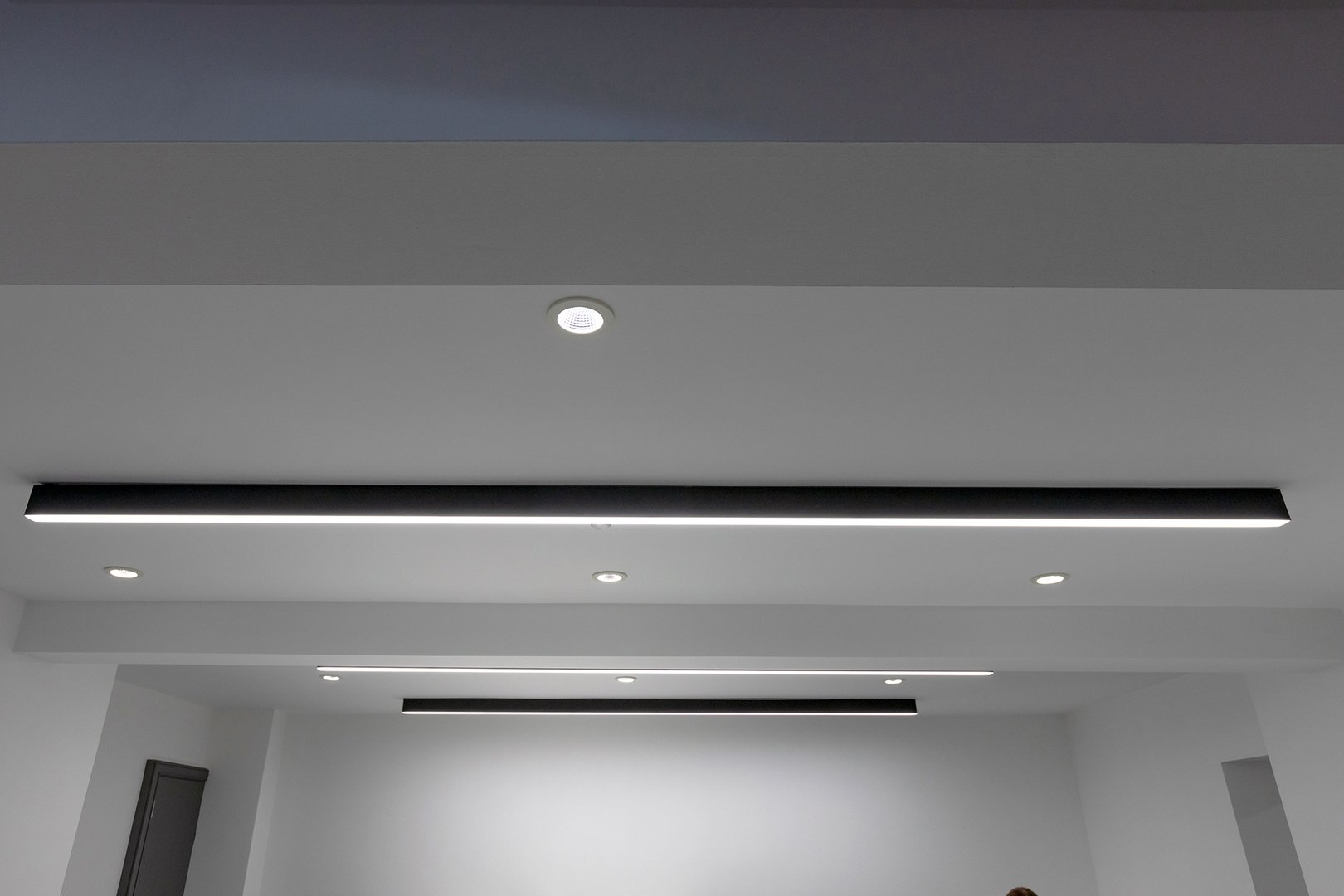 Clerkenwell showroom with blac LED linear lighting and downlights close up.jpg